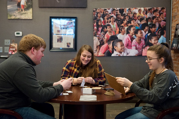(from left) JT Creswell, junior at College Heights Christian School, Connor Manley, senior, and Tessa Greathouse, junior, work on tags on Wednesday at Rapha House.<br /> Globe | Roger Nomer