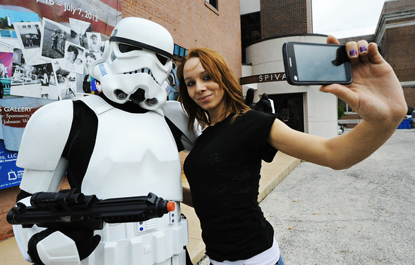 """Globe/T. Rob Brown<br /> """"There's one, set for stun."""" James Kave, also known as Imperial stormtrooper TK-12275 with the 501st Legion out of Springfield, gets his photo taken with Star Wars fan Telicia Spurgeon of Joplin outside Spiva Center for the Arts during the Third Thursday Art Walk event, May 16, 2013. A group of five 501st members dressed up as famous Star Wars characters, including Darth Vader and bounty hunter Boba Fett, for the event."""