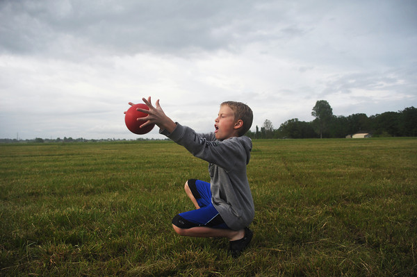 Globe/Roger Nomer<br /> Thomas Black, a fourth grader at St. Mary's Elementary, plays a game of catch on the future grounds of the school following Thursday's groundbreaking.