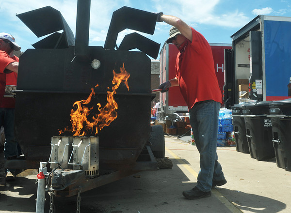 Globe/Roger Nomer<br /> With hot coals waiting, Jason Betts, Carthage, a nurse manager with Tyson, cooks food for volunteers at Southgate Baptist Church on Wednesday morning.