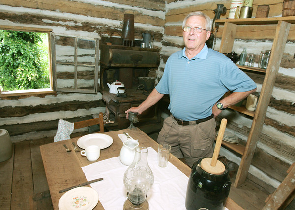 Globe/Roger Nomer<br /> Jim Hall, president of the Baxter Springs Historical Society, talks about the interior of a 1870's log cabin at the historical museum.