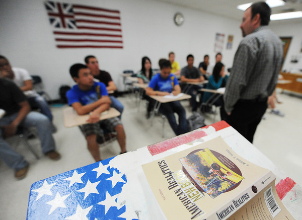 """Globe/T. Rob Brown<br /> Jason Navarro, Wheaton High School social studies teacher, leads, but not from the patriotic podium that holds his """"American Realities"""" textbook, the discussion in his History 107 class on modern history from 1877 to present as they discuss the history of computers Wednesday afternoon, May 1, 2013. Navarro was recently named Teacher of the Year by the Missouri State History Day. This class is dual credit with Crowder College."""