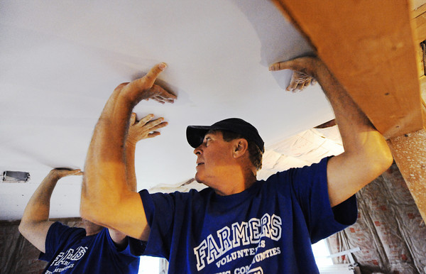 Globe/T. Rob Brown<br /> Dennis Lorch, Farmers Insurance Group Board of Governors member, helps hold up a piece of sheetrock while volunteering to help rebuild the 85th Rebuild Joplin home Tuesday morning, May 21, 2013.