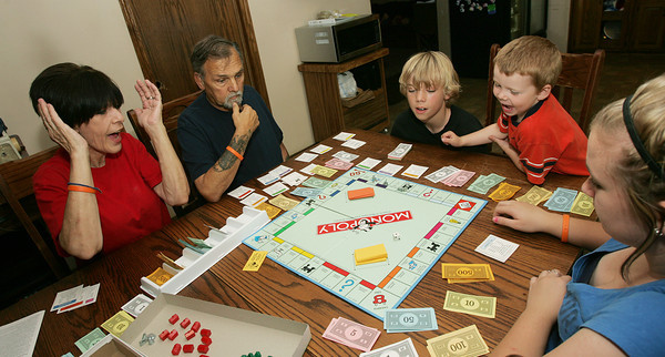 Globe/Roger Nomer<br /> (from left) Sandi, Mike, Kyle, 11, Isaac, 4, and Jaci, 15, Simpson play a board game on Thursday afternoon.
