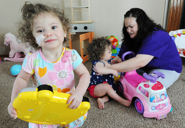 Globe/T. Rob Brown<br /> Triplet Lauren carries a toy around the living room as her mother Jayme Harper entertains triplet Addison nearby Thursday afternoon, May 16, 2013, in their Joplin home. The triplets who were born May 17, 2011, less than a week before the tornado, turn 2 today.