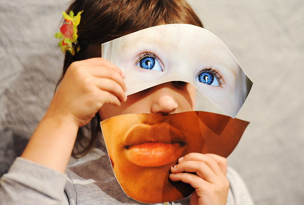 """Globe/T. Rob Brown<br /> """"Living art"""" Kayleah Silvers, 5, of Joplin, holds portions of face photos over her own at Spiva Center for the Arts during the Third Thursday Art Walk event, May 16, 2013. """"Diversity Masks"""" was part of the """"Art Workers"""" display at the center."""
