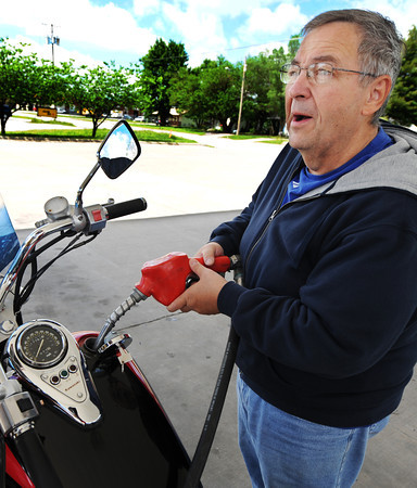 """Globe/T. Rob Brown<br /> Burton Masteller of Joplin watches the dollar amount go up as he tops off his motorcycle Wednesday morning, May 22, 2013, at the Casey's General Store on North Maiden Lane in Joplin. """"I ride my motorcycle to save gas,"""" Masteller said. """"I get 45 miles to the gallon on this and my Jeep only gets about 9-11. It's just not very good."""""""