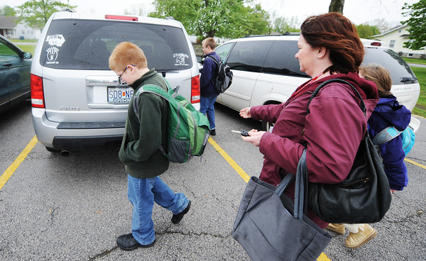 Globe/T. Rob Brown<br /> Sherri Petry, right, walks three of her children, from left, Timothy, 10, Sam, 11, and Lilli, 9, to the family vehicle after school Friday afternoon, May 3, 2013, before heading to Carl Junction Jr. High to pick up their older brother, Jonathan, 13.