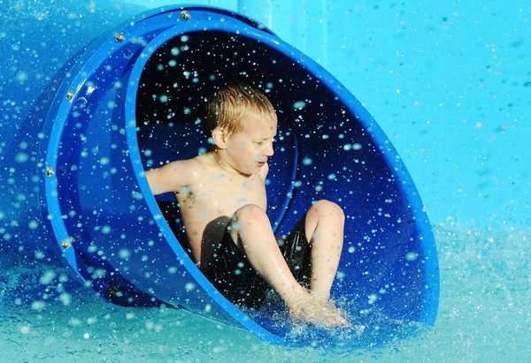 Globe/T. Rob Brown<br /> Luke Timi, 5, of Joplin, slides out into a downspray of water during open pool time Wednesday evening, May 22, 2013, at Cunningham Pool, as part of the tornado anniversary events. Joplin city pools officially open this weekend.
