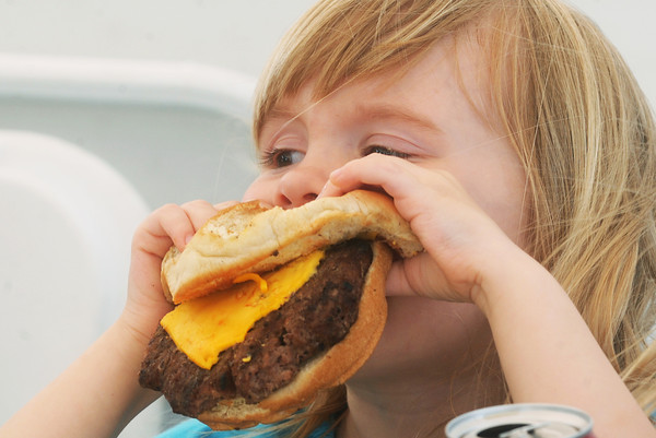 Globe/Roger Nomer<br /> Violet Haut, 3, Oronogo, chows down on a large hamburger during at benefit for Moore, Okla., on Friday afternoon at the Probation and Parole Office on Rangeline Road.
