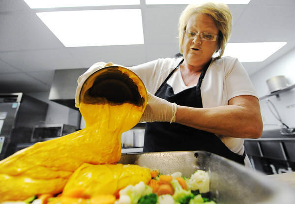 Globe/T. Rob Brown<br /> Sandra King, Boys & Girls Club kitchen manager, prepares a meal Thursday afternoon, May 9, 2013, including cooked vegetables and cheese.