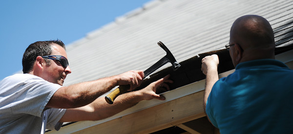 Globe/T. Rob Brown<br /> Stephen Crane, left, and Jack Quinn, both Boyd Metals employees, install a guard under the shingles on a home in the 100 block of North Sergeant for Rebuild Joplin Monday afternoon, May 13, 2013.