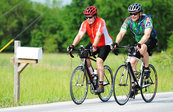 "Globe/T. Rob Brown<br /> Andy Perigo of Neosho and Dan Distler of Carl Junction ride their bicycles Saturday morning, May 18, 2013, down Newman Road just east of Joplin for JoMo Nola, ""riding to bring families home."""