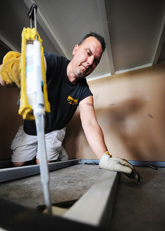 Globe/T. Rob Brown<br /> Twister Safe driver/installer Earl Spillman injects an epoxy into freshly drilled holes while installing a Twister Safe Tuesday afternoon, May 28, 2013, at a home in southern Neosho.