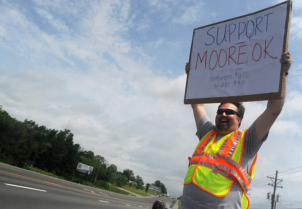 Globe/Roger Nomer<br /> Steve Norman, a probation and parole officer, holds up a sign promoting a benefit for Moore, Okla., on Friday afternoon at the Probation and Parole Office on Rangeline Road.