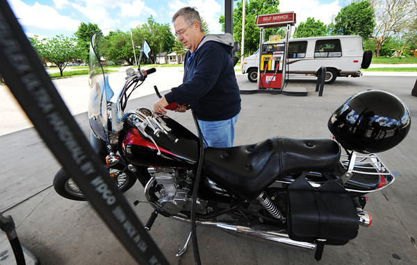 """Globe/T. Rob Brown<br /> Burton Masteller of Joplin finishes topping off his motorcycle Wednesday morning, May 22, 2013, at the Casey's General Store on North Maiden Lane in Joplin. """"I ride my motorcycle to save gas,"""" Masteller said. """"I get 45 miles to the gallon on this and my Jeep only gets about 9-11. It's just not very good."""""""
