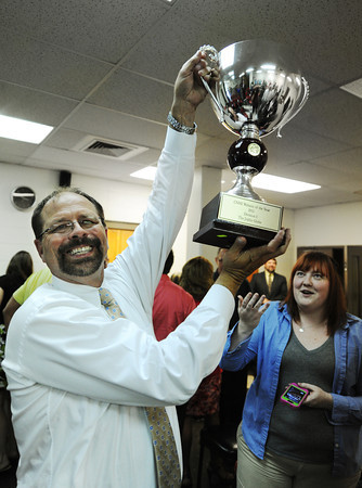 Globe/T. Rob Brown<br /> Joplin Globe Publisher Mike Beatty lifts up the newspaper's trophy for CNHI Website of the Year.