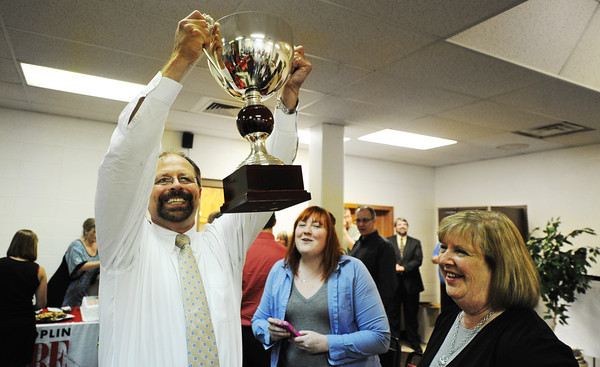 Globe/T. Rob Brown<br /> Joplin Globe Publisher Mike Beatty holds up the newspaper's trophy for CNHI Website of the Year as Alexandra Nicolas and Editor Carol Stark look on.