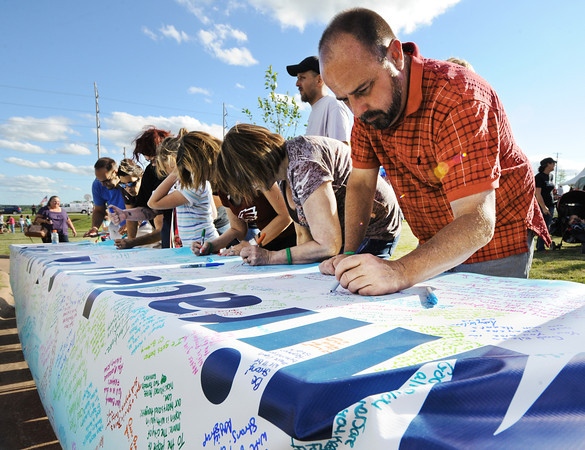 """Globe/T. Rob Brown<br /> Joe Royer of Joplin signs a banner that reads """"The Miracle of the Human Spirit"""" in support of Moore, Okla., during the second anniversary events of the Joplin tornado Wednesday evening, May 22, 2013, at Cunningham Park."""