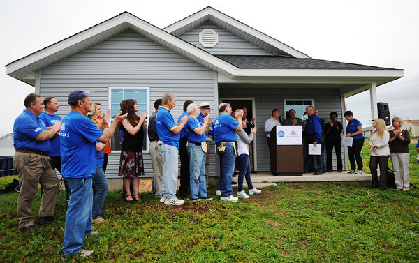 Globe/T. Rob Brown<br /> Volunteers and representatives (at left) from Farmers Insurance Group clap as the announcement is made for Farmers volunteers to help with the 85th Rebuild Joplin home Tuesday morning, May 21, 2013, outside the home.