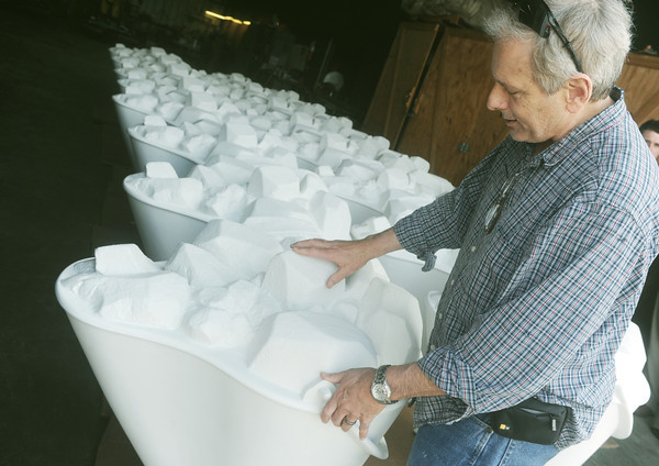Globe/Roger Nomer<br /> Pittsburg artist Rod Dutton examines the blank coal buckets ready for painting on Thursday afternoon.