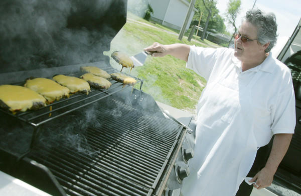 Globe/Roger Nomer<br /> Debbie Grimm, from Granny Shaffer's restaurant, prepares cheeseburgers at the Webb City Farmers Market on Tuesday morning.