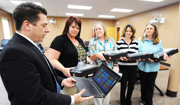 Globe/T. Rob Brown<br /> Brian Crouse, left, executive director of Missouri Math & Science Coalition, hands one of several Lenova Yoga 13 touchscreen laptops to (from left) Lisa Simmons, teaching and learning coach at Joplin's middle schools, Joyce Hale, seventh-grade science teacher at East Middle School, Belinda Vaness, Joplin High School science teacher, and Peggy Holland, special education in the science department at Joplin High School. The laptops were donated by Lenova to the coalition.