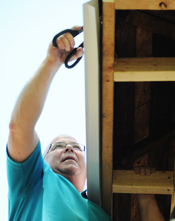 Globe/T. Rob Brown<br /> Jack Quinn, Boyd Metals employee, installs a guard under the shingles on a home in the 100 block of North Sergeant for Rebuild Joplin Monday afternoon, May 13, 2013.