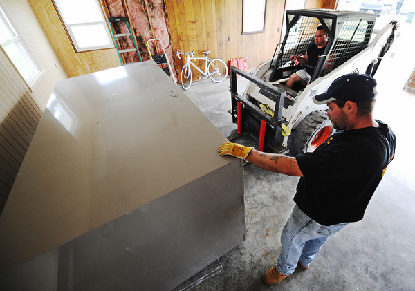 Globe/T. Rob Brown<br /> Twister Safe driver/installer Earl Spillman (above, right) and installer Matthew Ogle of Neosho deliver a custom-built Twister Safe Tuesday afternoon, May 28, 2013, to a home in southern Neosho.