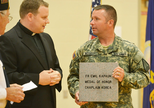 Globe/Roger Nomer<br /> National Guard SFC Marc McCully shows a paver dedicated to Emil J. Kapuan to Our Lady of Lourdes Catholic Church Associate Pastor Fr. Adam Keiter during a Memorial Day event at the Pittsburg State on Monday.