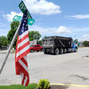 A debris removal truck drives by a flag hung on a street sign at 15th and Military in Baxter Springs on Wednesday.<br /> Globe | Laurie Sisk