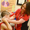 Globe/Roger Nomer<br /> Stacey Whitney helps Mason Bickerstaff, first grade, with an icepack at Carl Junction Elementary School on Thursday morning.