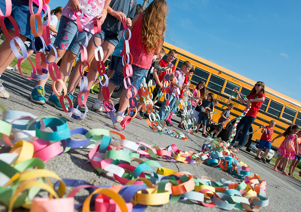 Globe/Roger Nomer<br /> Carl Junction second grade teacher Sarah Hauck helps organize lengths of paper chain for students on Thursday morning. Students contributed links to the chain for acts of kindness throughout the year.