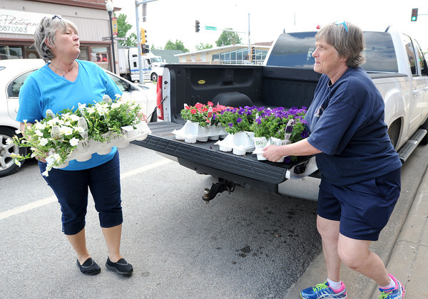 Cathy Bolek, left and Sue Gast unload flowers Wednesday to be planted in downtown Baxter Springs as part of a beautification project. The woman see rebuilding after the tornado as an opportunity to better the entire town.<br /> Globe | Laurie Sisk