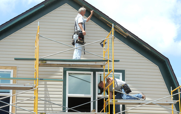 A construction crew installs new siding on a house near 10th and washington streets in Baxter Springs on Wednesday.<br /> Globe   Laurie Sisk
