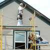 A construction crew installs new siding on a house near 10th and washington streets in Baxter Springs on Wednesday.<br /> Globe | Laurie Sisk