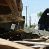 Globe/Roger Nomer<br /> Anita Leyba, Joplin, looks into a debris pile as she searches for lost photos from the Baxter Springs tornado on Friday. Leyba was volunteering with National Disaster Photo Rescue, who returned to her several photos she lost in the Joplin tornado three years ago.