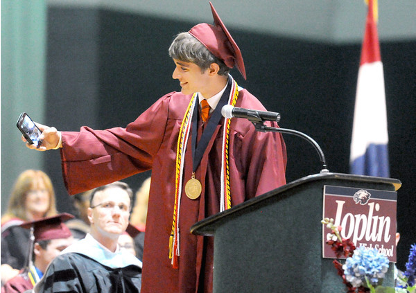 Matthew Riechman-Bennett pauses to take a selfie before addressing the Joplin High School senior class during graduation ceremonies on Sunday at the Leggett & Platt Athletic Center. Riechman-Bennett was one of three Summa Cum Laude graduates, in addition to Drew Cox and Adelle Kanan.<br /> Globe | Laurie Sisk