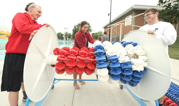 From the left: Nathan Landes, Lindsay Murray and Matt Kersey roll lane rope for storage last week in preparation for the opening of Schifferdecker Pool.<br /> Globe | Laurie Sisk