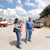 From the left: Cherie Schenker, her three-year-old daughter Suzanna Schenker and Tom Goff stand in the middle of downtown McCune on Friday. Both Schenker and Goff are part of a committee to try to entice more businesses to open in the tiny town of about 400 people.<br /> Globe | Laurie Sisk