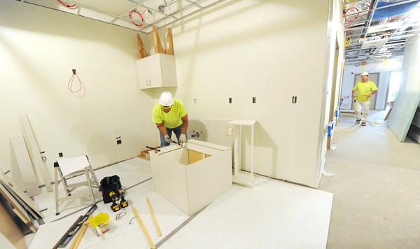 Workers begin installing the numerous cabinets built in an on-site cabinetry shop at the new Mercy Hospital on Wednesday.<br /> Globe | Laurie Sisk