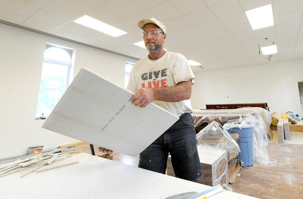 Rick Satzler installs new ceiling tiles inside the sanctuary of the Church of the Nazarene in McCune, Kan. on Friday. Satzler was a member of the last graduating class at McCune High School in 1979.<br /> Globe | Laurie Sisk