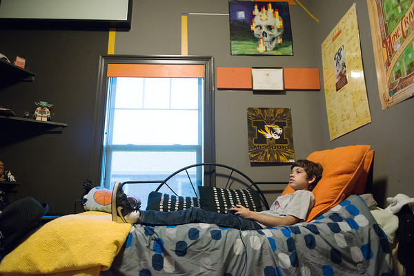 Globe/Roger Nomer<br /> Augie Ely, 12, plays a video game in his room of his family's Extreme Makeover house on Tuesday. The family has updated his room since the makeover.