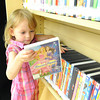 Suzanna Schenker,3, browses through the collection of DVDs at the McCune Osage Township Library on Friday.<br /> Globe | Laurie Sisk