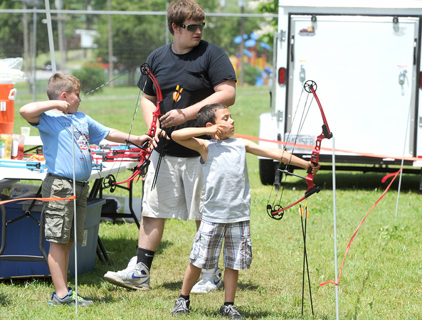 Scout leader Michael Linsteadt, 19, center, assists Cub Scout Ronny Klein, 8, left and Brayden Seitz, six, as they learn about archery during the Kindergarten Taste of Scouting event on Saturday at Landreth Park. About 100 youth attended the event, which was designed to get younger boys interested in scouting.<br /> Globe | Laurie Sisk