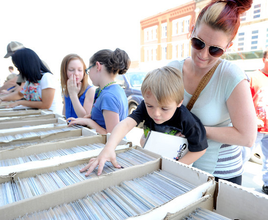 Alisha Davis helps her four-year-old son, Mike Davis as he skims through boxes of bargain comic books at Hurley's Heroes on  Saturday. Saturday was National Free Comic Book Day, an event scheduled for the first Saturday in May.<br /> Globe | Laurie Sisk