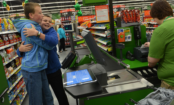 Globe/Roger Nomer<br /> Brothers Justin, 14, left, and Brandon, 13, hug for joy at being the first customers at the new Wal-Mart Neighborhood Market on Thursday morning.