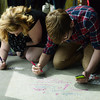 Globe/Roger Nomer<br /> Joplin High seniors Angelina Millard and Alex Chesney write messages on the floor of the new Joplin High School on Friday morning.