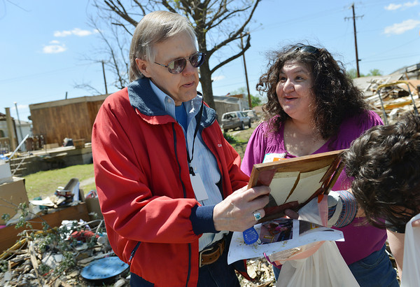 Globe/Roger Nomer<br /> Gale Karber looks over a photo frame found by Julie Carettini, Joplin, as she was volunteering with National Disaster Photo Rescue on Friday in Baxter Springs. Carettini and other volunteers found several items belonging to Karber in the debris.