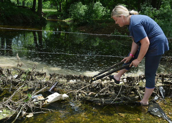 Globe/Roger Nomer<br /> Patricia Holloway, Pierce City, looks at a dead fish along Clear Creek near Pierce City on Wednesday.